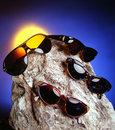 Four sunglasses over a nice stone Stock Photo