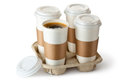 Four take-out coffee in holder. One cup is opened. Royalty Free Stock Photos