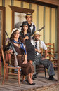 Four tough gangsters male and female sitting with weapons Royalty Free Stock Photos