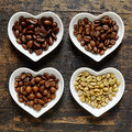 Four types of coffee beans in heart shaped bowls Royalty Free Stock Photo