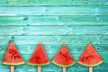 Four watermelon slice popsicles on blue wood background with copy space, summer fruit concept Royalty Free Stock Photo