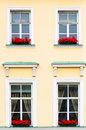 Four windows with red flowers close up Stock Photos