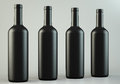 Four wine bottles blank on grey background Royalty Free Stock Photos