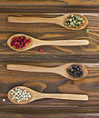 Four wooden spoons with color peppers Royalty Free Stock Photo