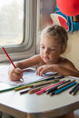 Four-year girl drawing with pencils at a table in a train Royalty Free Stock Photo