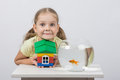 Four-year girl holding a toy house and sits in front of a goldfish Royalty Free Stock Photo