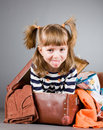 Four year girl joyfully sits in an old suitcase with toys and clothes Royalty Free Stock Photo