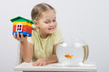 The four-year girl sits with a toy house in front of a goldfish Royalty Free Stock Photo