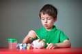 Four years old boy painting his piggy toy Stock Photo