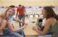 Four young adults cheering in a bowling alley Royalty Free Stock Photography