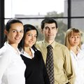 Four young businesspersons standing in a row Royalty Free Stock Photos