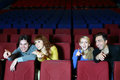 Four young friends laugh and point finger at screen in cinema theater Royalty Free Stock Images