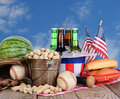 Fourth of july picnic table ready for a celebration cold beer in an uncle sam hat watermelon peanuts baseball and hot dog buns Stock Photos