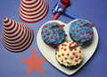 Fourth th of july party celebration with red white and blue chocolate cupcakes on white heart plate and usa american flags with Stock Images