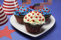 Fourth th of july party celebration with red white and blue chocolate cupcakes on white heart plate and usa american flags with Royalty Free Stock Photo