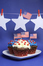Fourth th of july party celebration with red white and blue chocolate cupcakes on white heart plate and usa american flags with Stock Photography