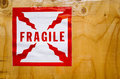 Fragile sticker a sign warning of contents on the side of a wood Royalty Free Stock Images