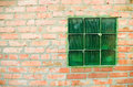 Fragment of brick wall with green glass window Stock Images