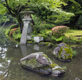 Fragment of japanese garden with stone lantern and big rocks covered with moss a standing in water flowers trees in background Stock Image