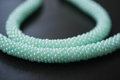 Fragment of a necklace of mint color on a wooden background close up Stock Photo