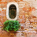Fragment of red vintage old brick wall with round window. Royalty Free Stock Photo