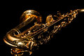 Fragment of a saxophone on a black background lying in dark colors Stock Images