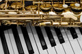 Fragment of the saxophone lying on piano keys Stock Images