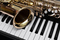 Fragment of the saxophone lying on piano keys Royalty Free Stock Photos