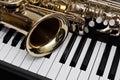 Fragment of the saxophone lying on piano keys Royalty Free Stock Photos