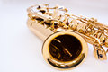 A fragment of a saxophone lying on white surface Stock Image