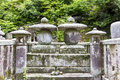 Fragment of a traditional temple graveyard japan with stone monuments and lanterns Stock Photos