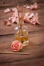 Fragrance sticks or scent diffuser with rose flowers on wooden background Stock Images