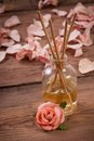 Fragrance sticks or scent diffuser with rose flowers on wooden background Royalty Free Stock Photo