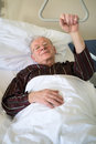 Frail senior man lying in a hospital bed on ward recuperating from an illness or operation resting with his glasses on and Royalty Free Stock Photography