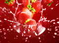 Fraise tombant dans le sort de jus Photo stock