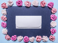 Frame of colorful paper roses laid out on a dark background with an envelope middle top view close up place text in the for Royalty Free Stock Photo