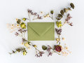 Frame of dry flowers and envelop on white background. Flat lay, top view Royalty Free Stock Photo