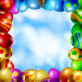 Frame of easter eggs made with various colors and patterns on blue sky with white fluffy clouds background Stock Images