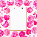 Frame made of purple roses, ranunculus and clipboard on white background. Flat lay, top view. Floral pattern of pink flowers Royalty Free Stock Photo