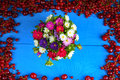 Frame made of red currant and cherry with flower bouquet Royalty Free Stock Photo