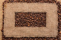 Frame made of rough burlap lies on coffee beans Royalty Free Stock Photo