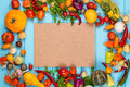 Frame of organic vegetables on blue wooden background. Organic food concept. Space for text. Royalty Free Stock Photo