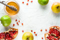 Frame of pomegranate, pomegranate seeds and apples with honey for the Rosh Hashanah Royalty Free Stock Photo