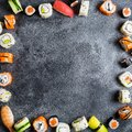 Frame with set of Japanese food on dark background. Sushi rolls, nigiri, raw salmon steak, rice and avocado. Flat lay. Top view Royalty Free Stock Photo