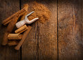 Frame with sticks and ground celyon cinnamon on wooden table Stock Images