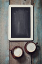 Framed blackboard and coffee small wooden with two cups of on wooden background Royalty Free Stock Image