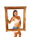 Framed girl a smiling pretty young woman in shorts and exercise bra standing for white background holding a big picture frame in Royalty Free Stock Photography