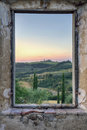 Framed view from an old window in abandoned stone house to a green tuscany landscape wit hills and cypresses Royalty Free Stock Photo