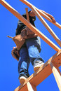 Framer standing on top of wall a carpenter with nail bags balancing a working in the trusses a house that is under construction Stock Images