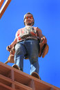 Framer standing on wall a carpenter wearing leather nail bags looking down a working the roof of a house that is under Royalty Free Stock Photos